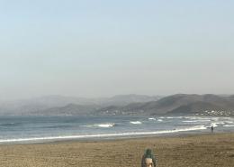 Fisherman walks on a sandy beach in Morro Bay California