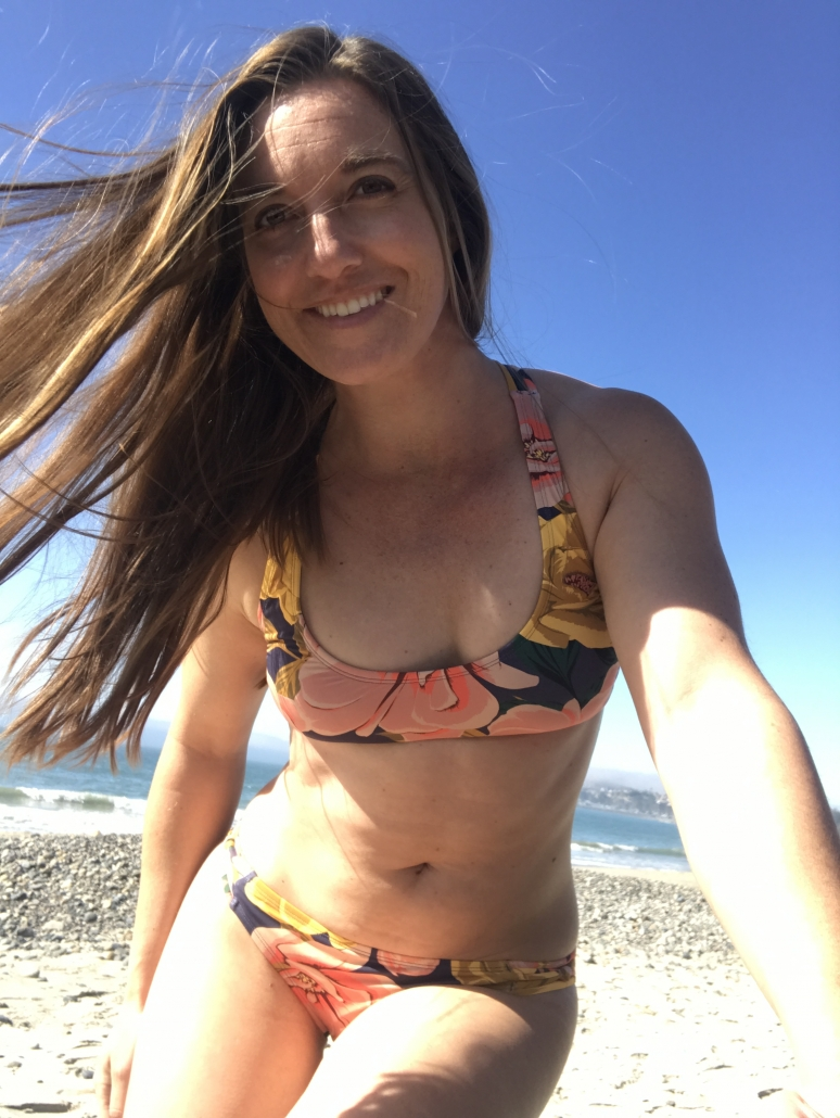 woman in bikini with floral print smiles on the beach in the sun
