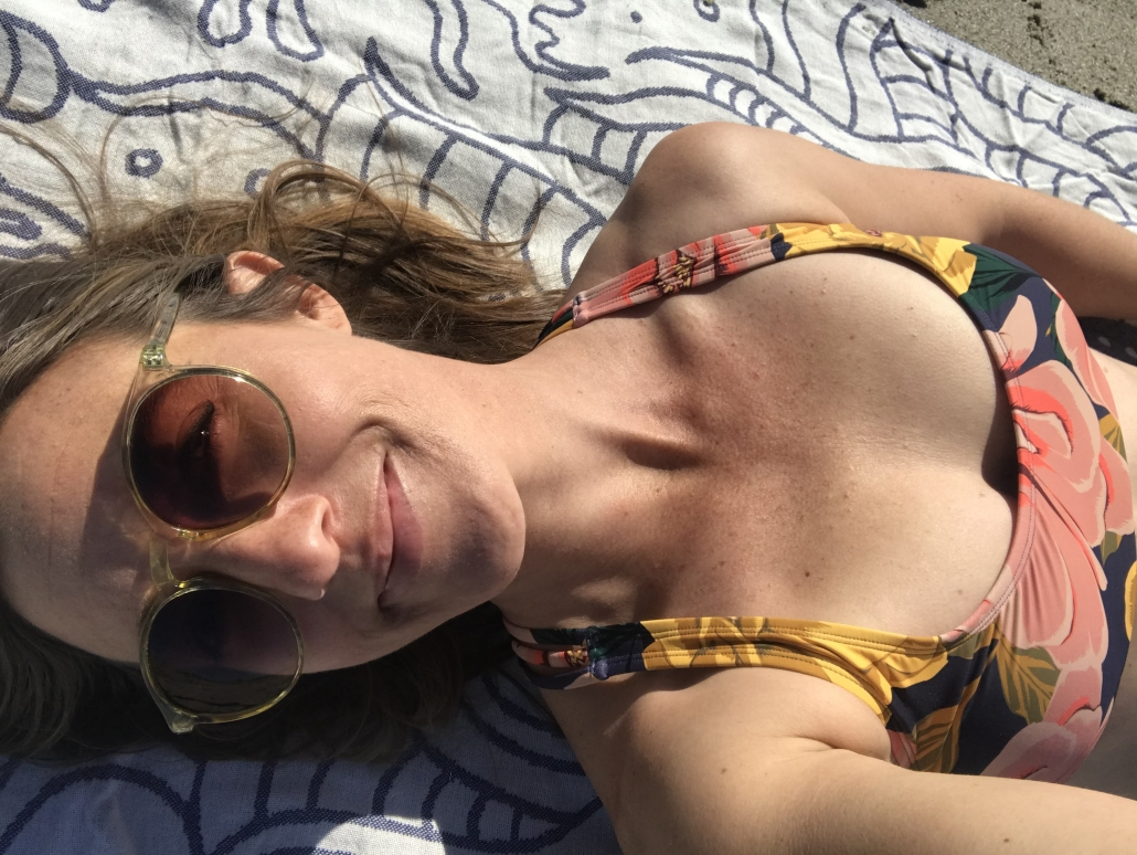 woman laying in the sun with Eidon bikini and sunglasses