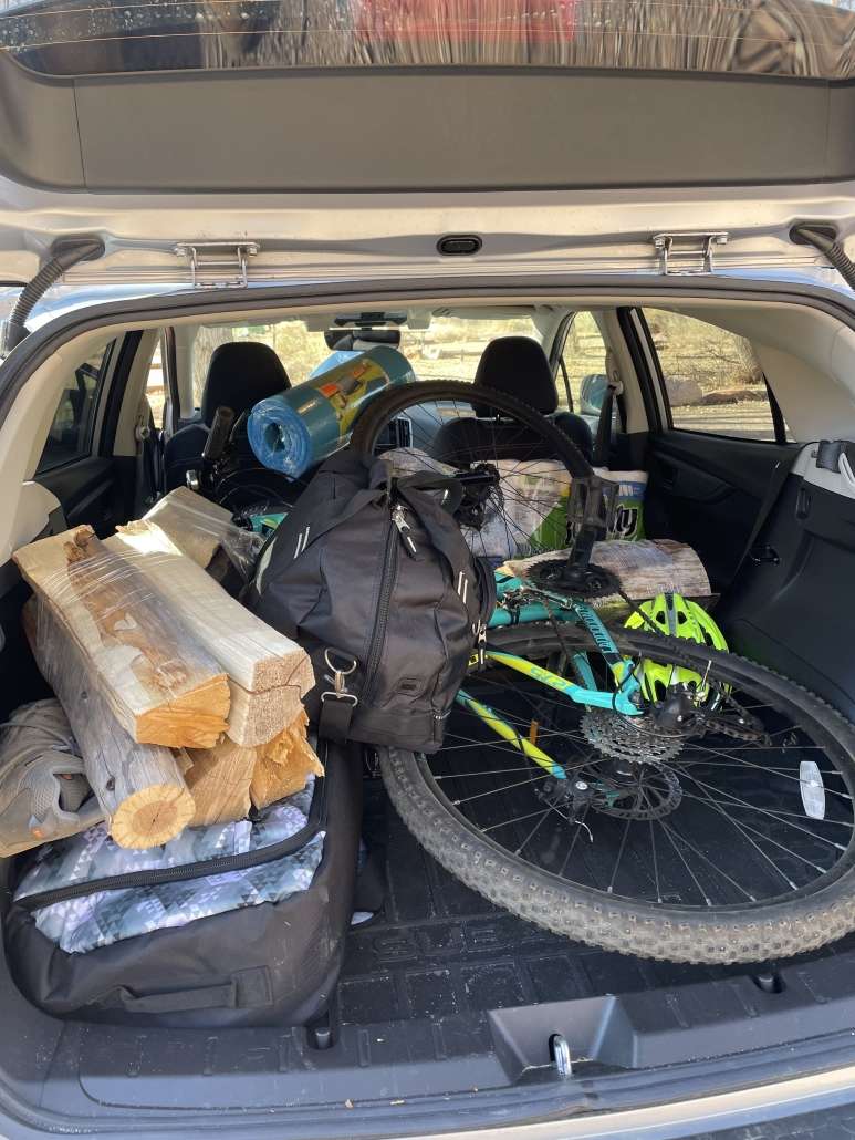 bike, firewood, snowboard and camping gear all piled in the back of a car