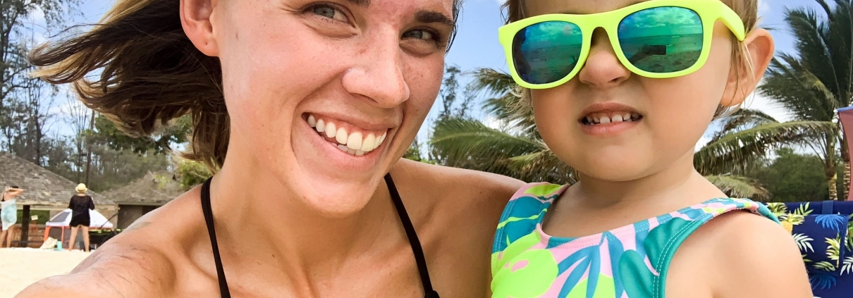 Kayla Pearson holds three year old daughter with sunglasses