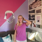woman with long blonde hair wearing a pink shirt and white shorts smiles while standing in front of a pink wall with a shark mouth painted on the wall