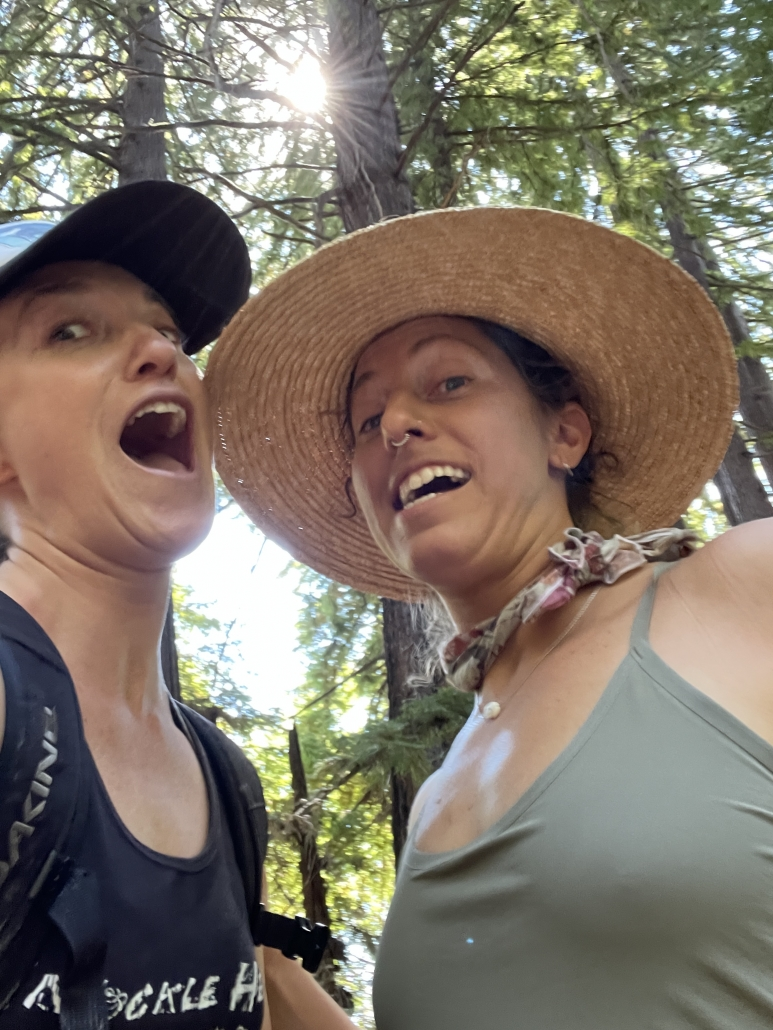 two girls standing in a forest making funny faces