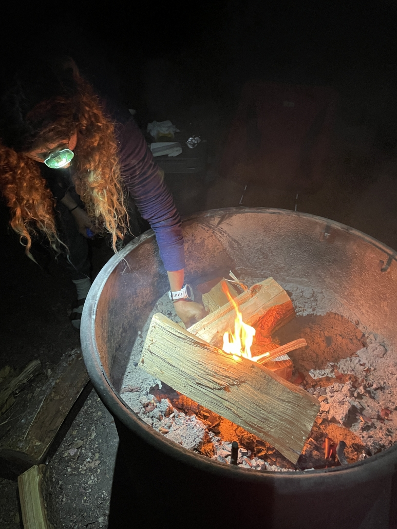 a girl wearing a headlamp tends to a campfire