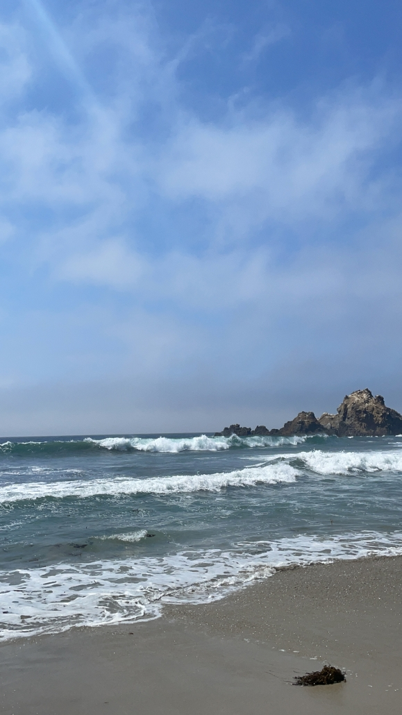 secluded beach with rocks and windy conditions in a partly cloudy sky
