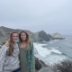 two girls wearing sweaters with arms around shoulders stand on a cliff in Big Sur Willow Creek smiling