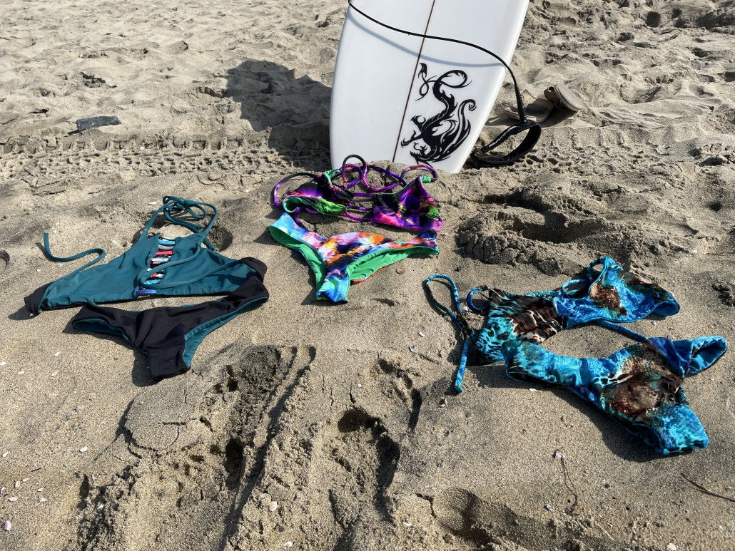 three bikinis sit in the sand in front of a white surfboard with a black dragon painted on it
