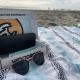 WoodRoze sunglasses sit on a sandcloud beach towel in Newport Beach, California