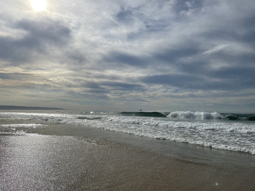 partly sunny Newport Beach with a wave in the background and sparkling sand