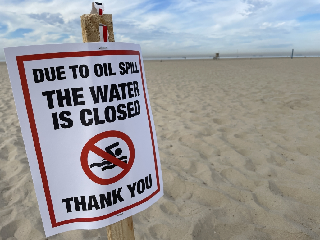 oil pill water is closed sign in sand in Newport Beach, California
